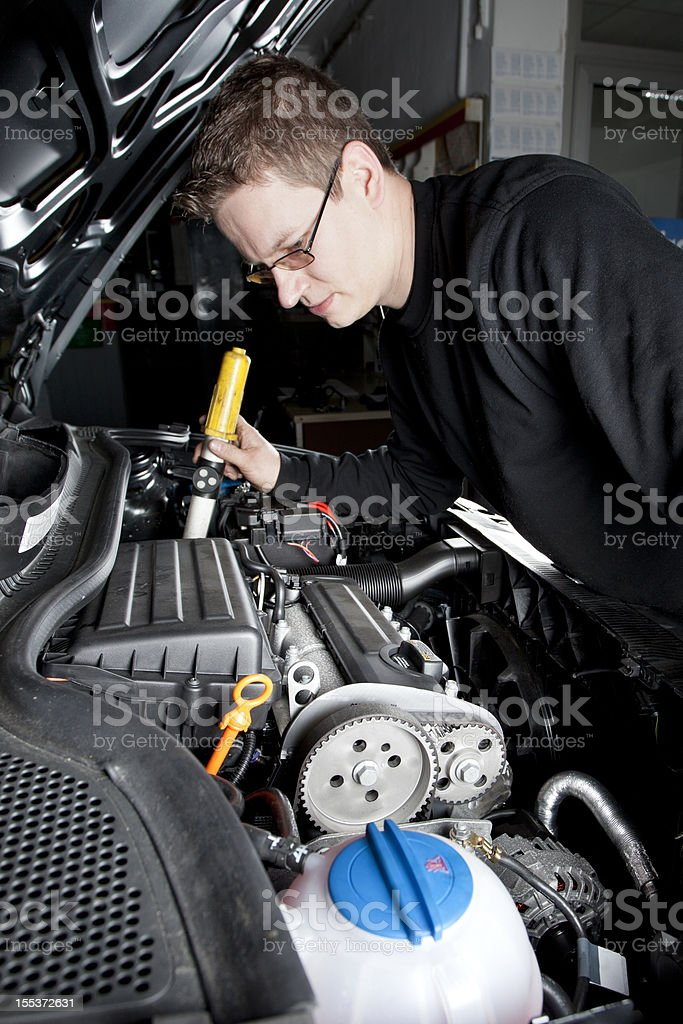 Mechanic is checking the engine of a modern car royalty-free stock photo