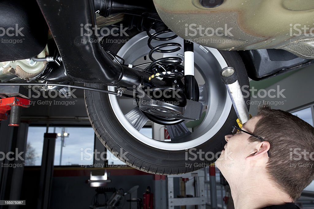 Mechanic is checking the shock absorbers of a modern car royalty-free stock photo