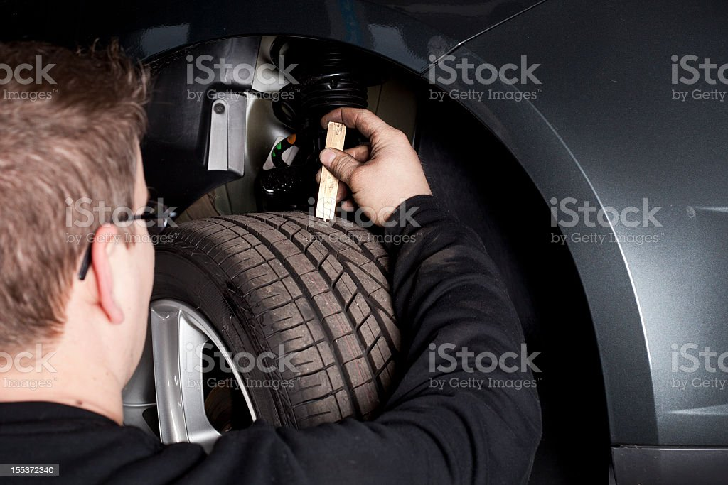 Mechanic is checking the skid depth of a tire royalty-free stock photo