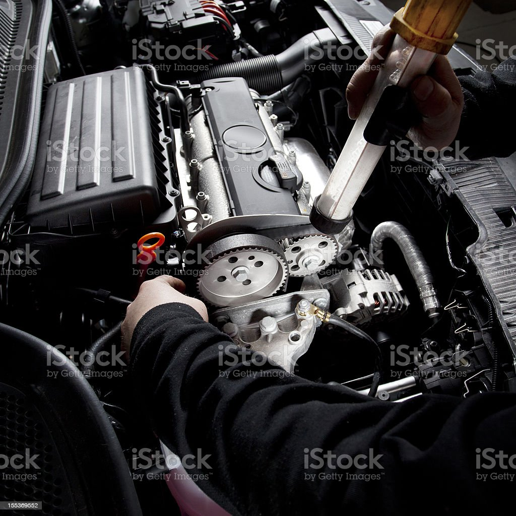 Mechanic is checking the timing belt of a modern car royalty-free stock photo
