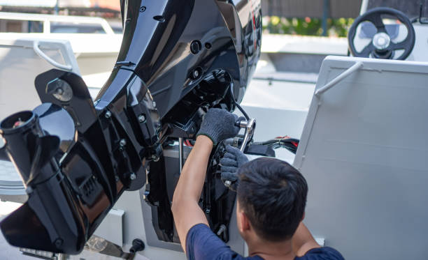 Mechanic is installing speed boat engine Mechanic is installing speed boat engine , a new engine on an aluminum boat. hull stock pictures, royalty-free photos & images