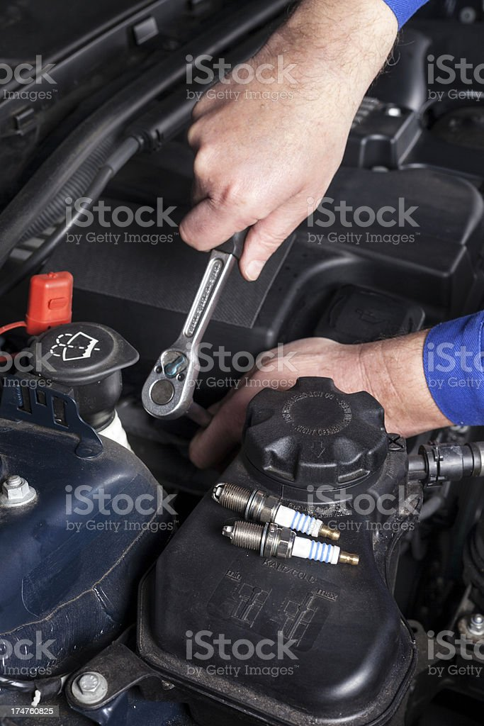 Mechanic is unscrewing the ignition plugs of a modern car royalty-free stock photo