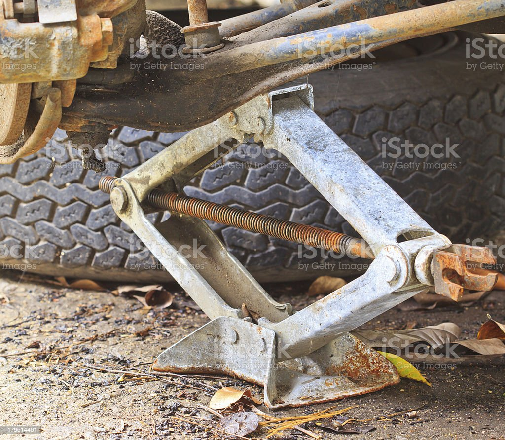 Mechanic lifting a car with jack-screw royalty-free stock photo
