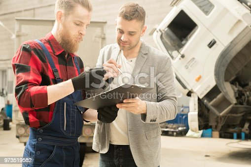 962888586 istock photo Mechanic Looking At Checklist With Client 973519582