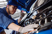 istock Mechanic man examining and maintenance via insurance system fix the engine a vehicle car hood, Safety inspection before customer drive on a long journey, transportation repair garage service center 1192846214
