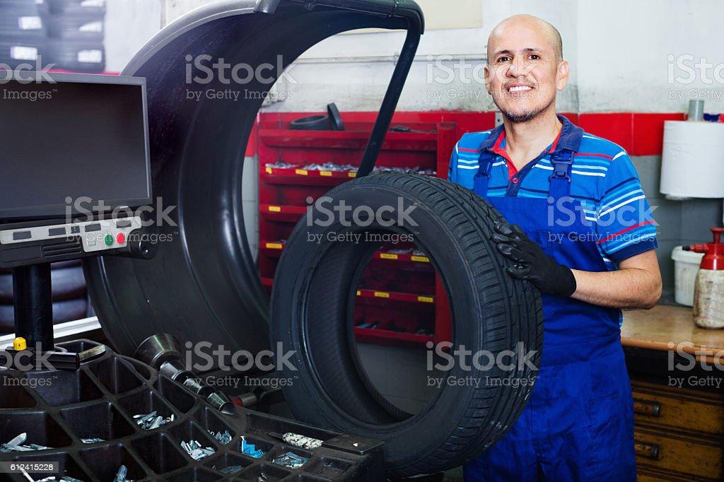 Mechanic man having car wheel on equilibrium control machinery stock photo