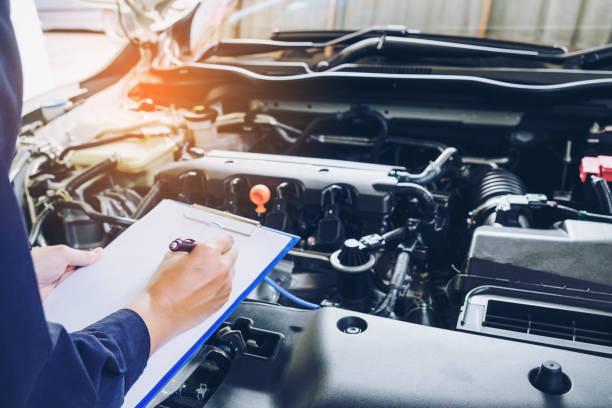 mechaniker mann hält zwischenablage und überprüf das auto - autowerkstatt stock-fotos und bilder