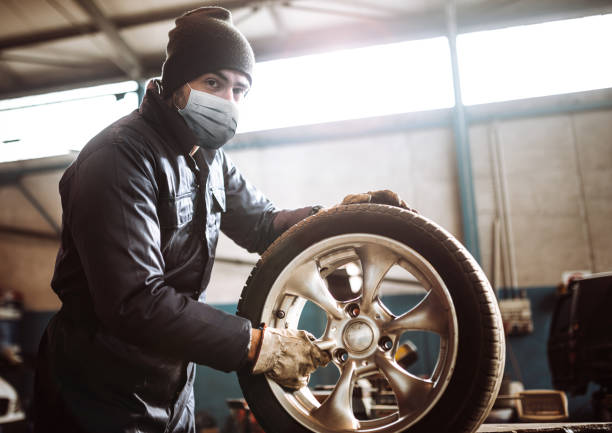 mechanic man repair a tire with a covid mask stock photo