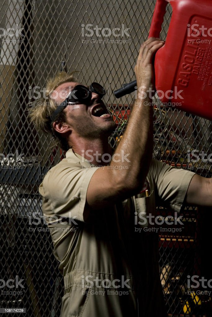 Mechanic Man Wearing Safety Goggles Drinking From Gasoline Can royalty-free stock photo