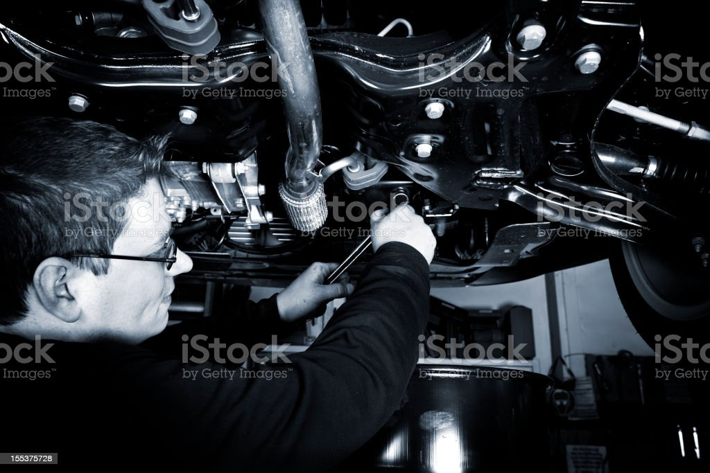 Mechanic opens the oil drain plug of a modern car royalty-free stock photo