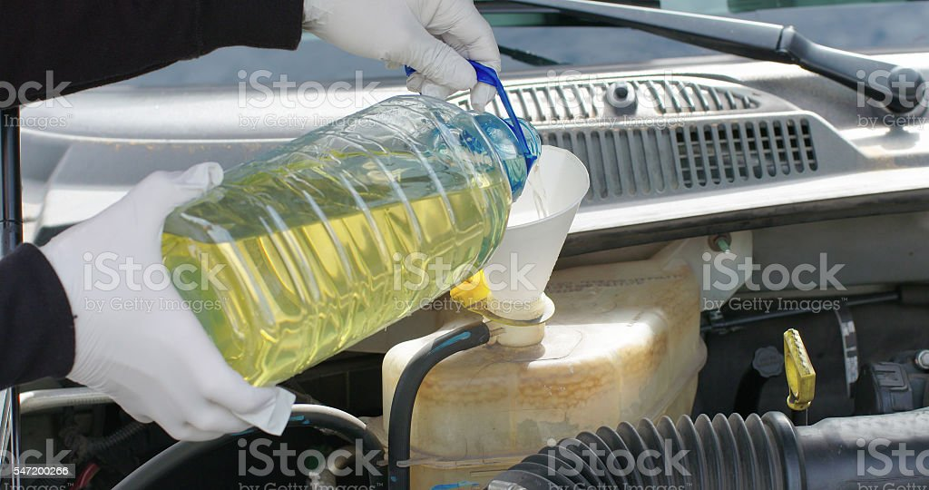 Mechanic or Driver Adding Coolant Antifreeze Additive To Car Engine stock photo