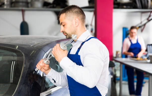 mechanic performing dent repair - dent stock pictures, royalty-free photos & images