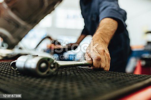 Hand of mechanic picking up a ratchet spanner from table in auto workshop. Mechanic working on garage with tools.