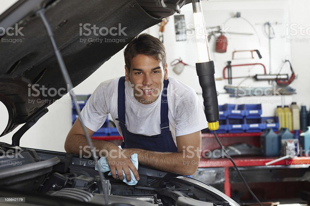 mechanic mechanic leaning on bonnet and looking at camera 30-39 Years Stock Photo