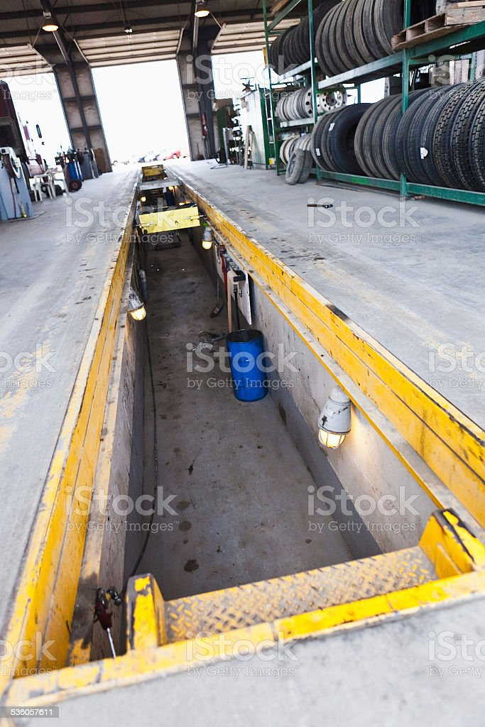 Mechanic pit in concrete floor of autobody shop stock photo