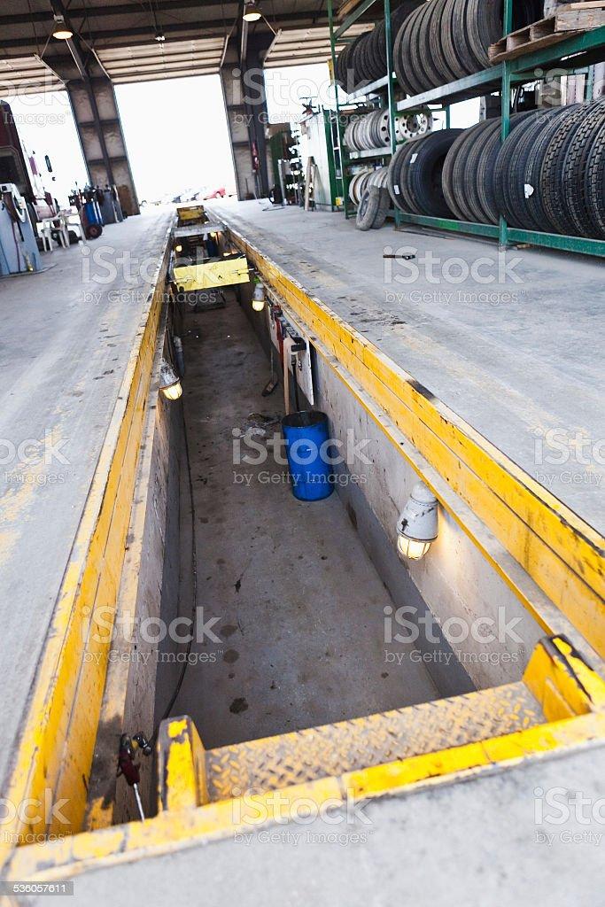 Mechanic pit in concrete floor of autobody shop stock photo