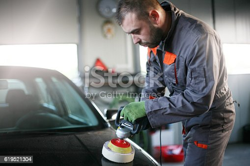 istock Mechanic polishing car. 619521304
