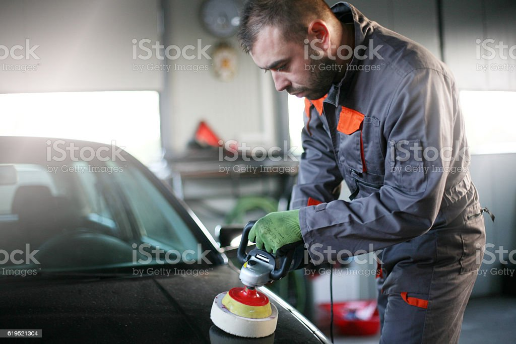 Mechanic polishing car. stock photo
