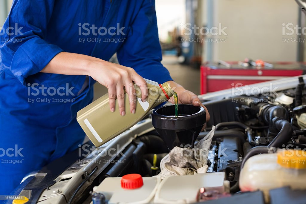 Mechanic pouring oil into car stock photo
