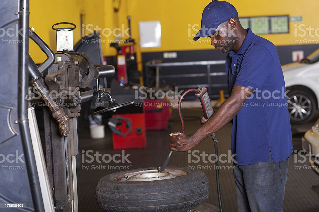 mechanic pumping car tyre stock photo