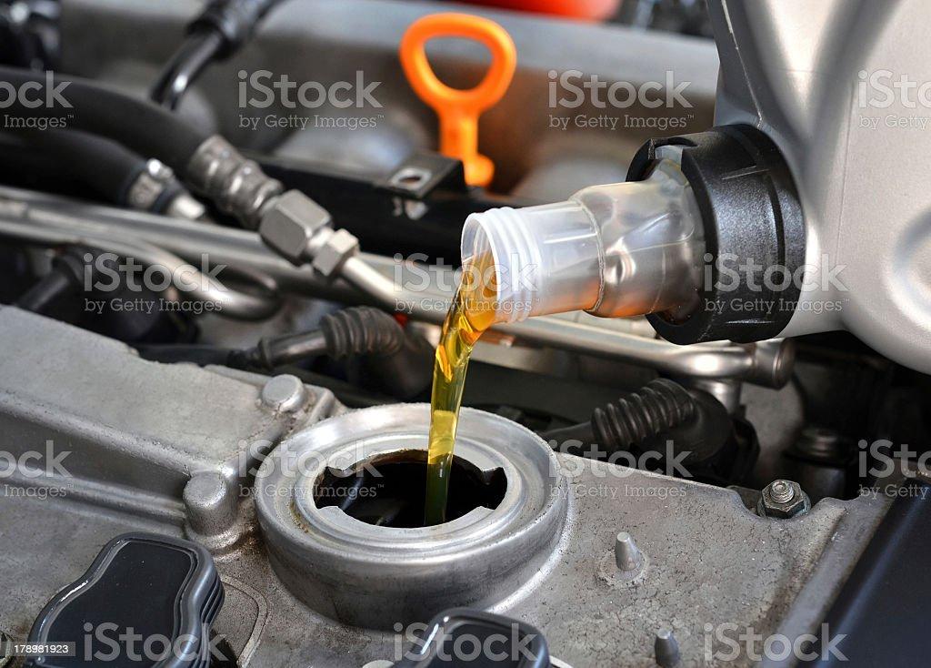Mechanic putting fresh motor oil in car stock photo