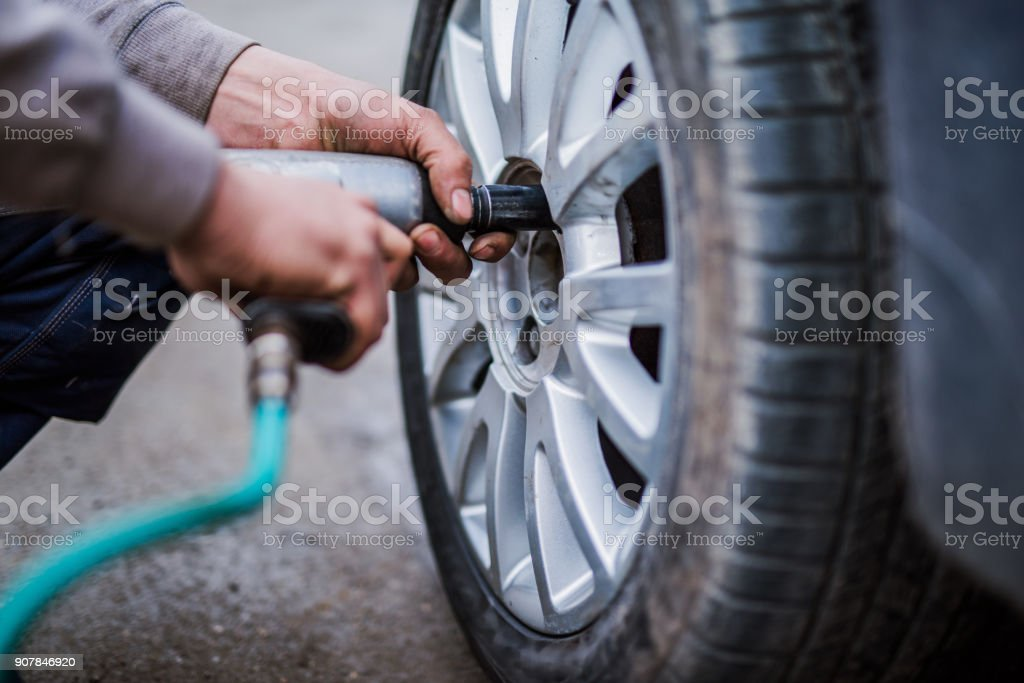Mechanic putting new wheels on a car using a handgun. stock photo