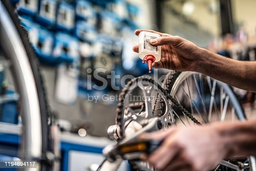Mechanic putting oil on bicycle chain close up.