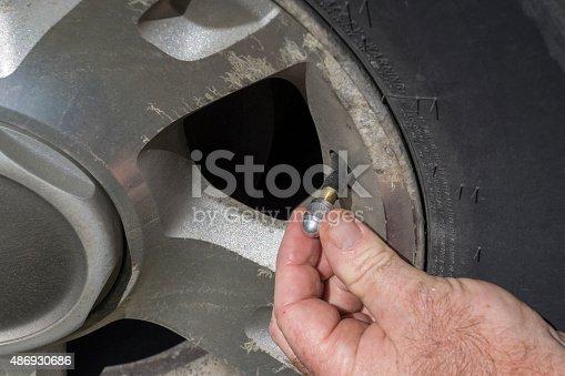 Mechanic putting on a new aluminum air valve stem cap for a customer.