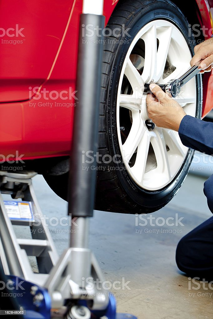 mechanic putting wheel on with jack royalty-free stock photo