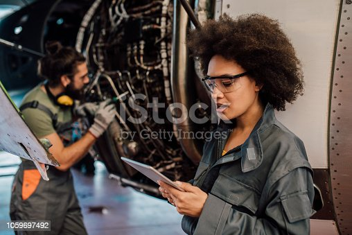 Young woman wearing protective uniform holding digital tablet