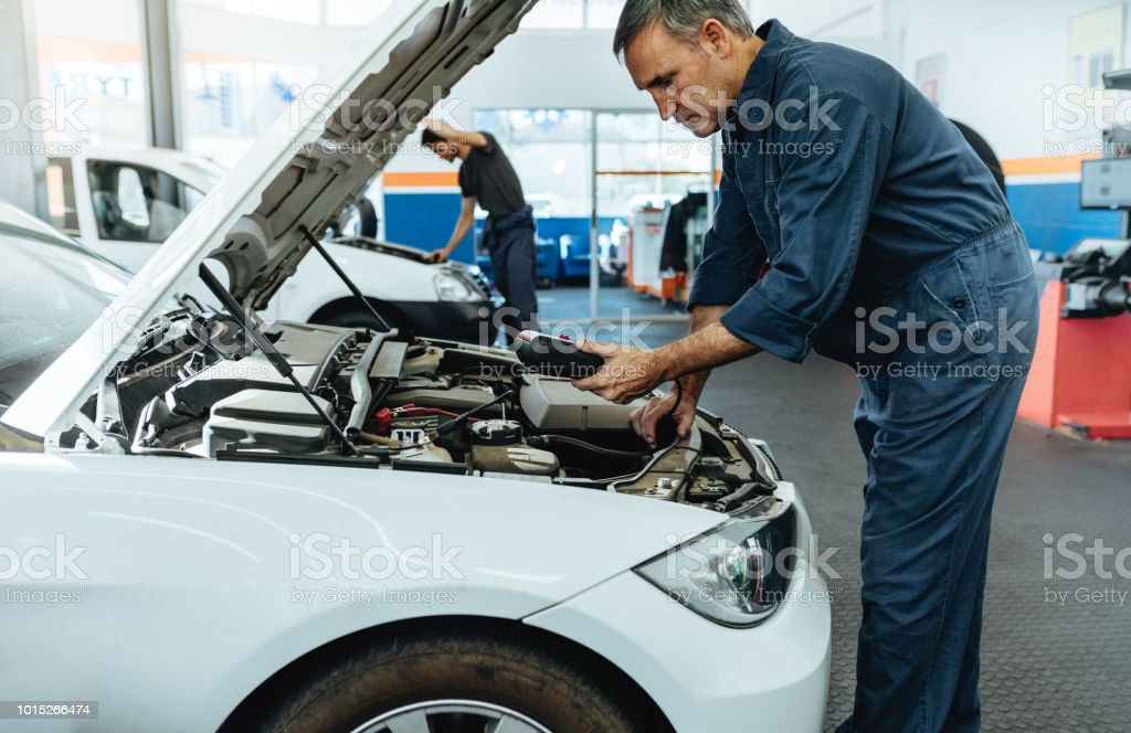 Mechanic reading the error codes with diagnostic device stock photo