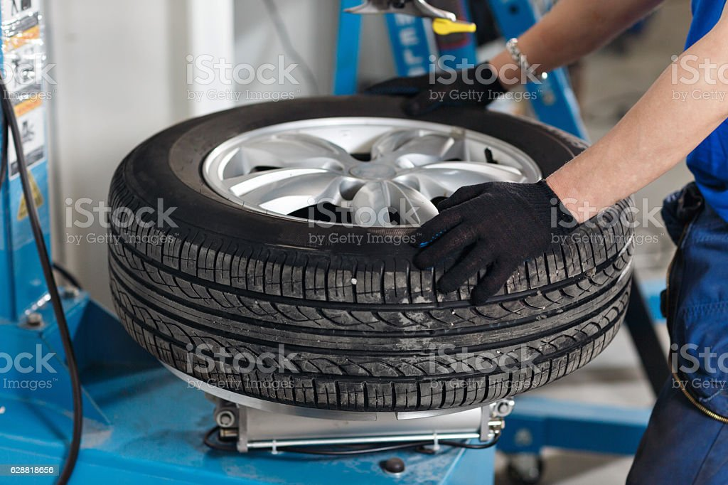 Mechanic removes car tire closeup. Machine for removing rubber from – Foto