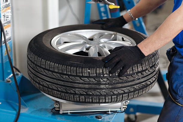 Mechanic removes car tire closeup. Machine for removing rubber from stock photo