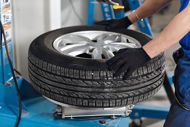 mechanic removes car tire closeup. machine for removing rubber from - alufelgen stock-fotos und bilder