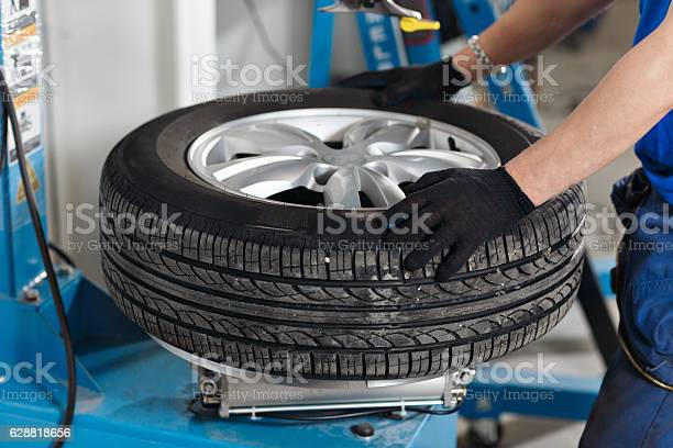 Mechanic Removes Car Tire Closeup Machine For Removing Rubber From Stock Photo - Download Image Now