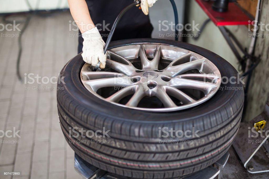 mechanic repair vehicle wheel tire, blow air into wheel tire in garage stock photo
