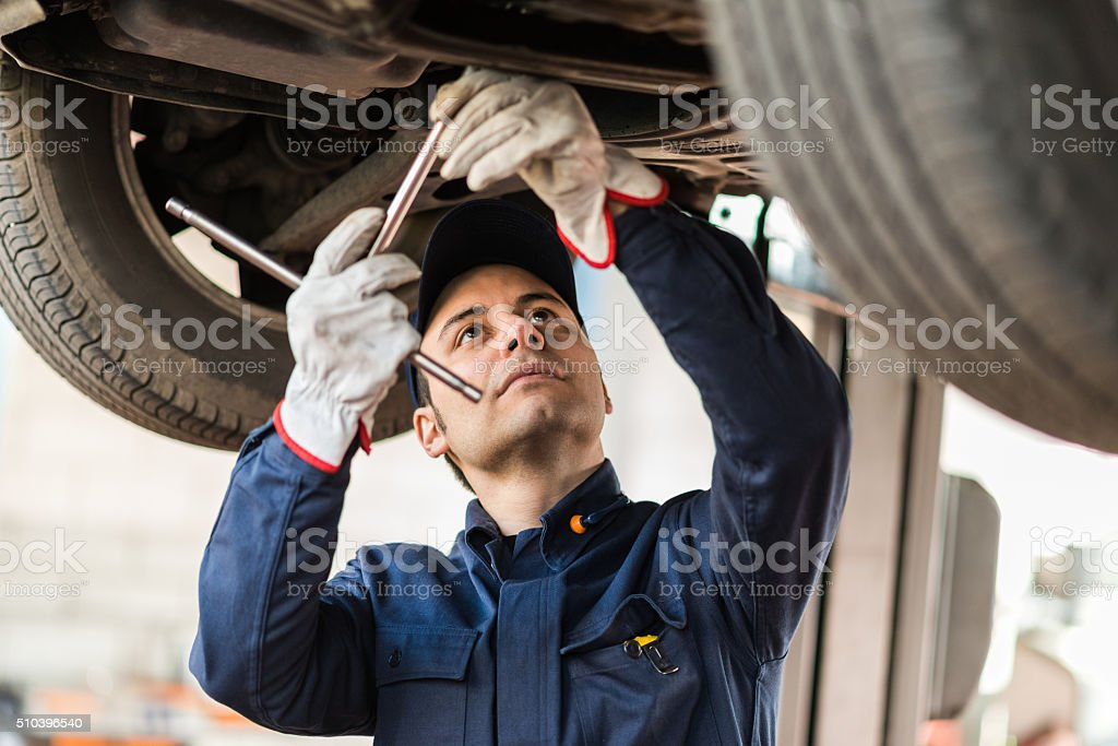 Mechanic repairing a lifted car stock photo