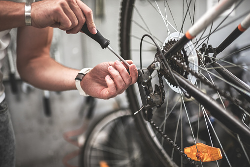 Close up shot on male hands inside bicycle store while repairing the gearshift on rear wheel of a mountain bike.