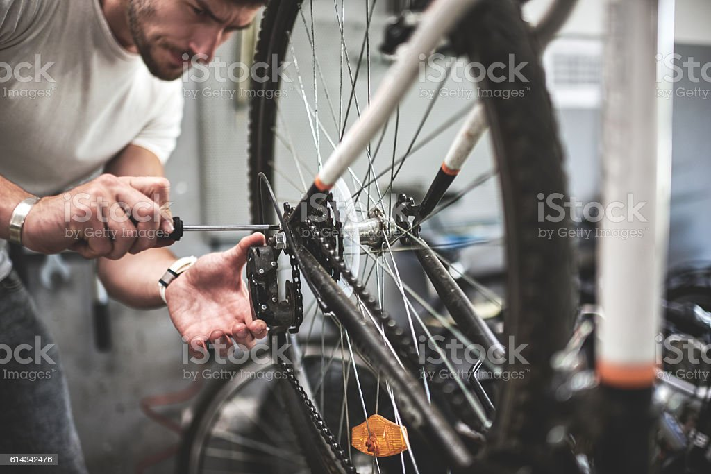Mechanic repairing bicycle transmission stock photo