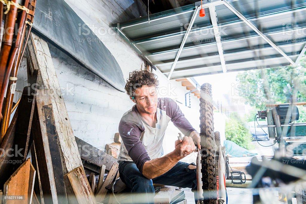 Mechanic repairing bicycle wheel in workshop royalty-free stock photo