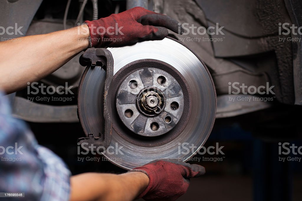 Mechanic repairing brakes on a car stock photo