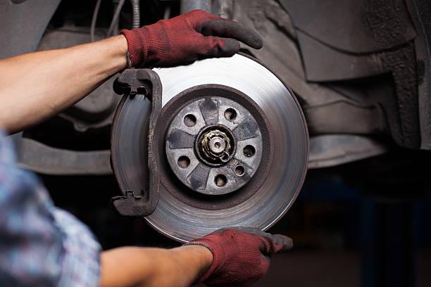 mechanic repairing brakes on a car - 剎車制 個照片及圖片檔