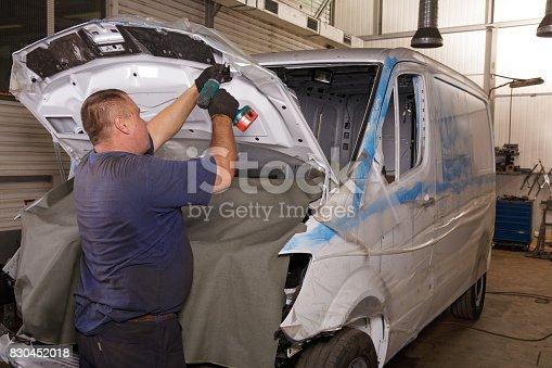 962888586 istock photo Mechanic repairing car with open hood 830452018