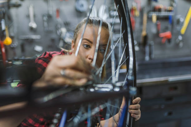 Mechanic repairing gears of bicycle Mechanic repairing gears of bicycle. Repair and tuning, adjustment, disc brake on a bicycle. Stylish bicycle mechanic woman doing his professional work in workshop. bicycle shop stock pictures, royalty-free photos & images