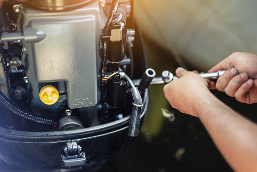 mechanic repairing inflatable motorboat engine at boat garage. Ship engine seasonal service and maintenance. Vessel motor with open cover.