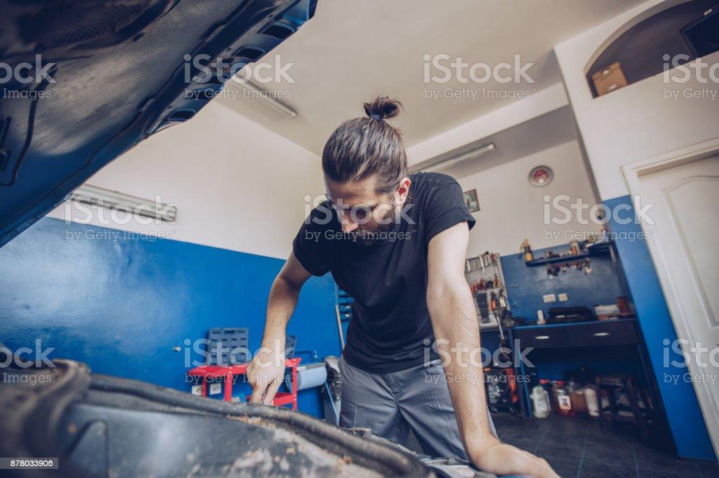 Mechanic repairing motor vehicle stock photo