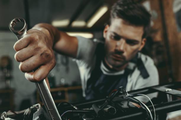 mechanic repairing motorbike - mechanic stock photos and pictures
