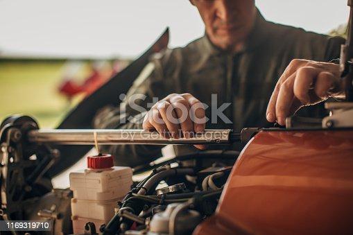One man, airplane mechanic and pilot repairing propeller airplane in airplane hangar.