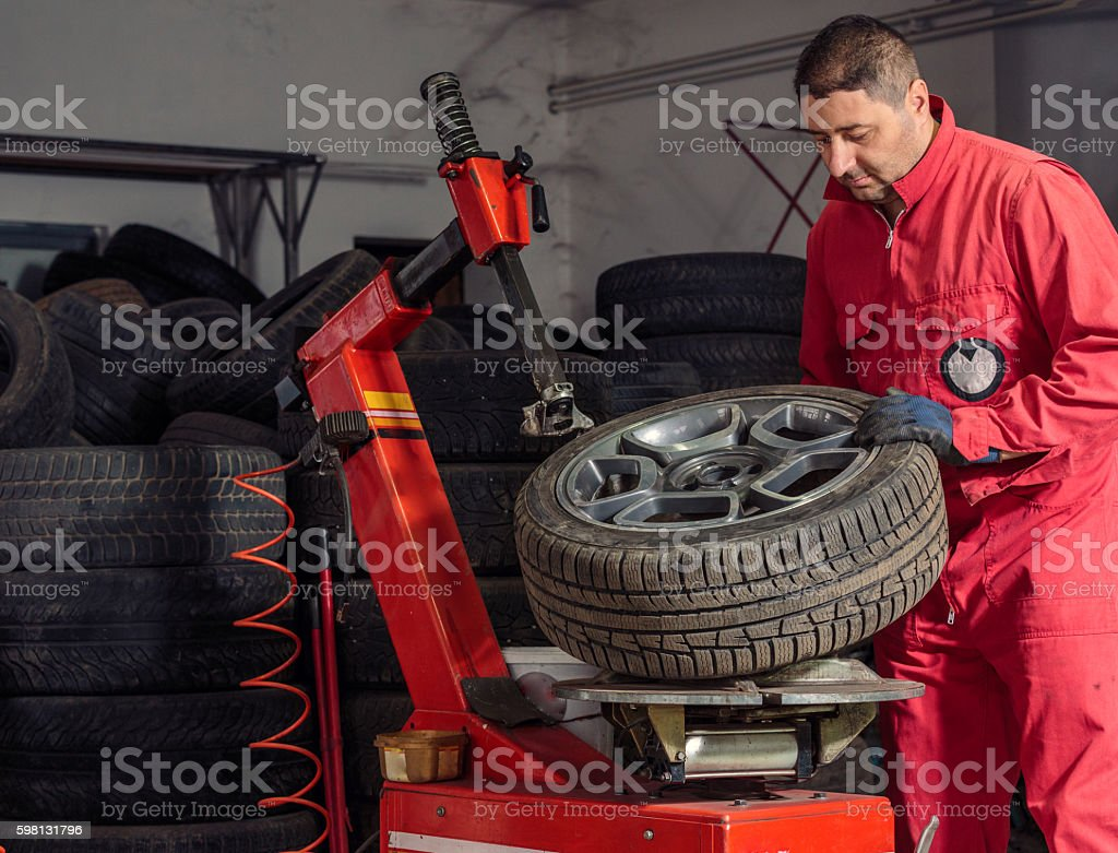Mechanic replacing a tire on the wheel - Photo