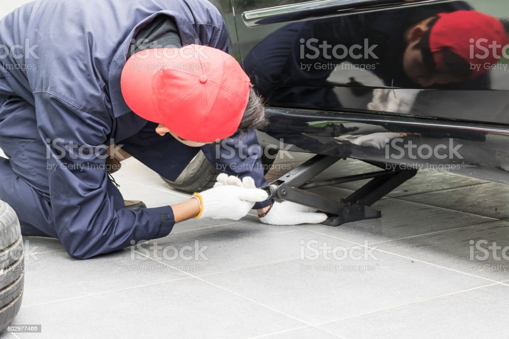 Mechanic replacing lug nuts changing tires on vehicle stock photo